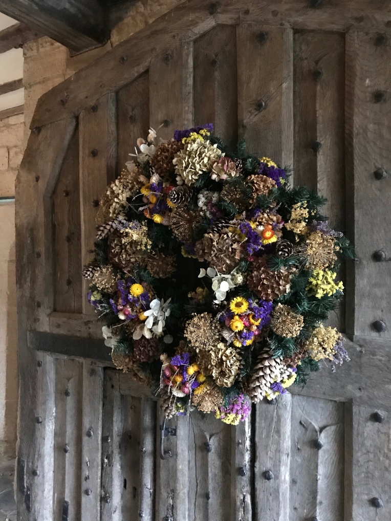 A large, dried flower Christmas wreath on the front door at Baddesley Clinton, Warwickshire