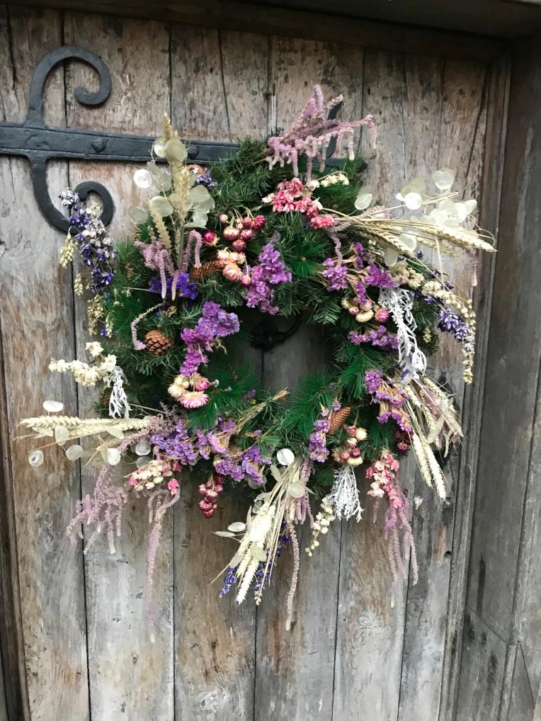 Christmas wreath on an old oak door at a Baddesley Clinton, Warwickshire.