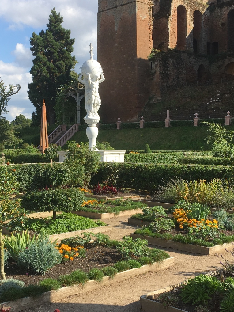An Elizabethan garden scene at Kenilworth Castle, with a small garden area featuring raised beds, topiary and the Atlas fountain.