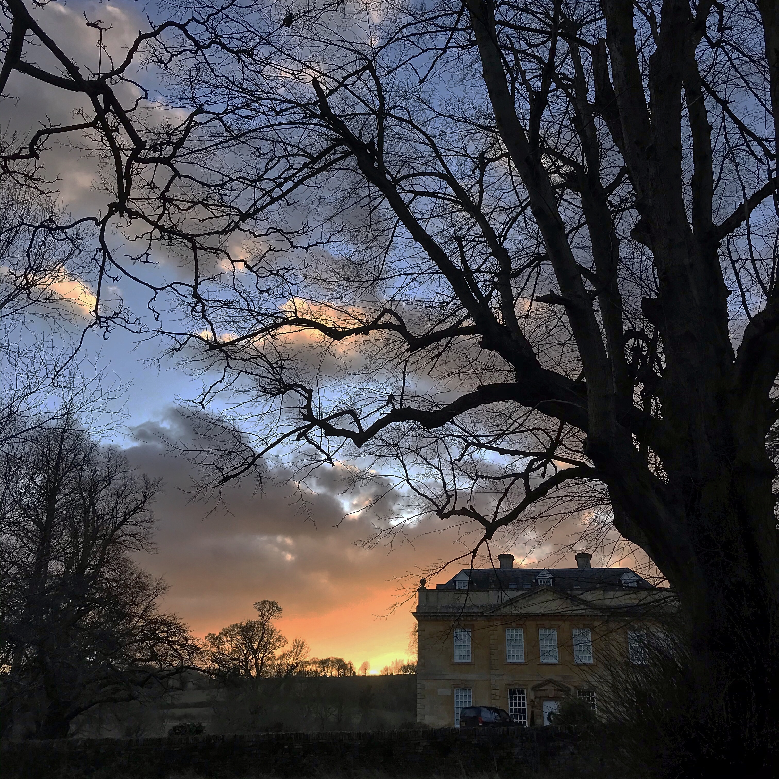 The sun setting behind Broadwell Manor in the Cotswolds, sunset