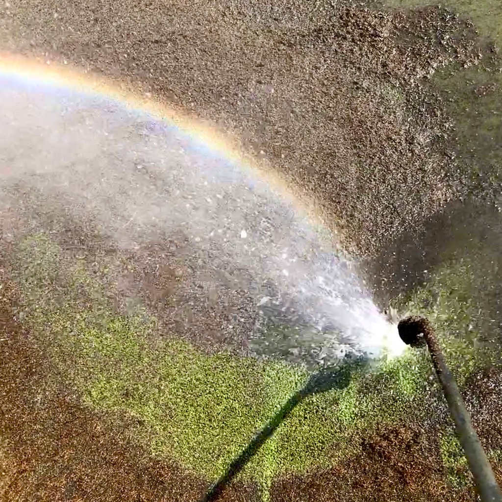Jet washing a tennis court in the sunshine