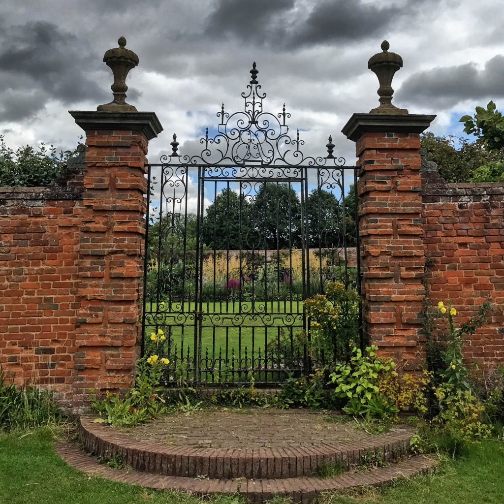 A view up arched red brick steps, to a very ancient wrought iron gate way At Packwood house in Warwickshire.