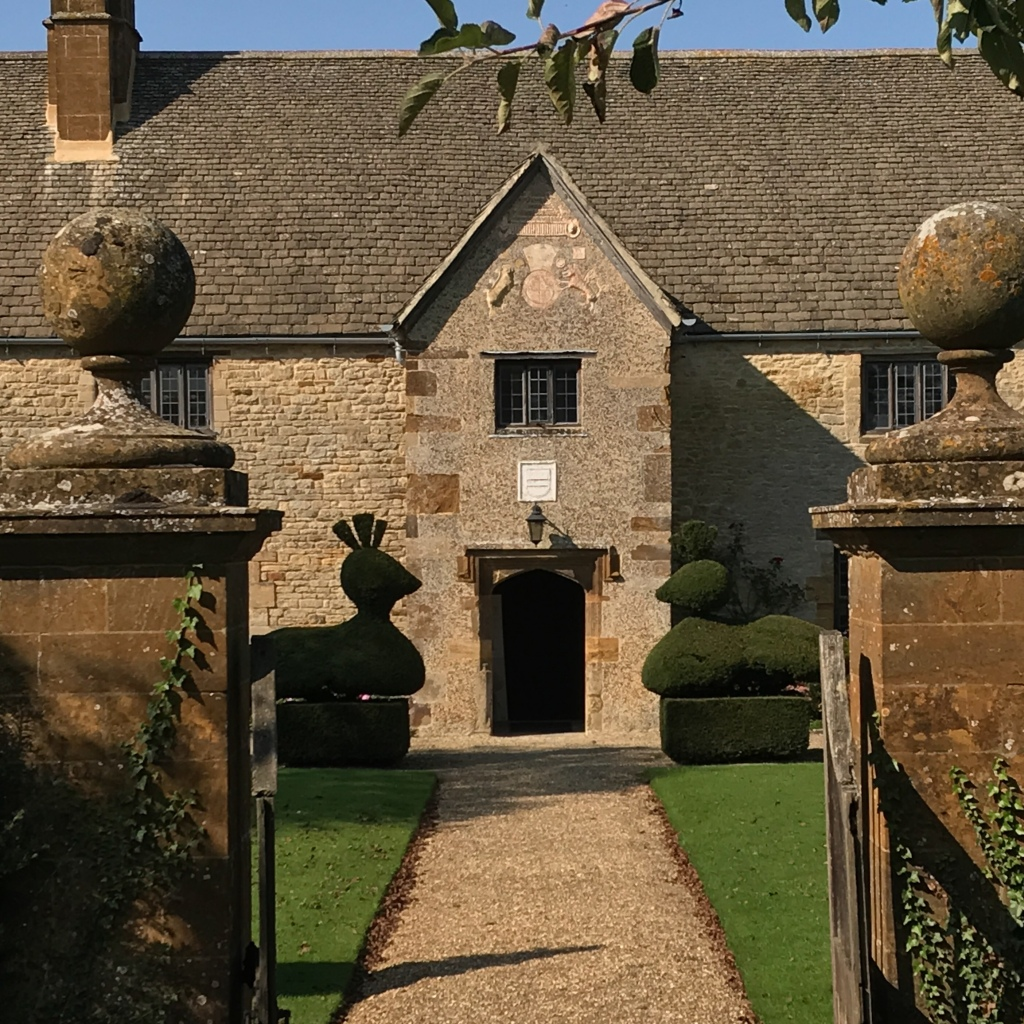 Sulgrave Manor, Northamptonshire.​ The front approach to the porch beyond peacock topiary specimens.