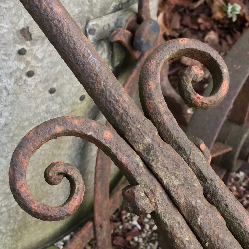 An ironwork scroll on a very old garden roller