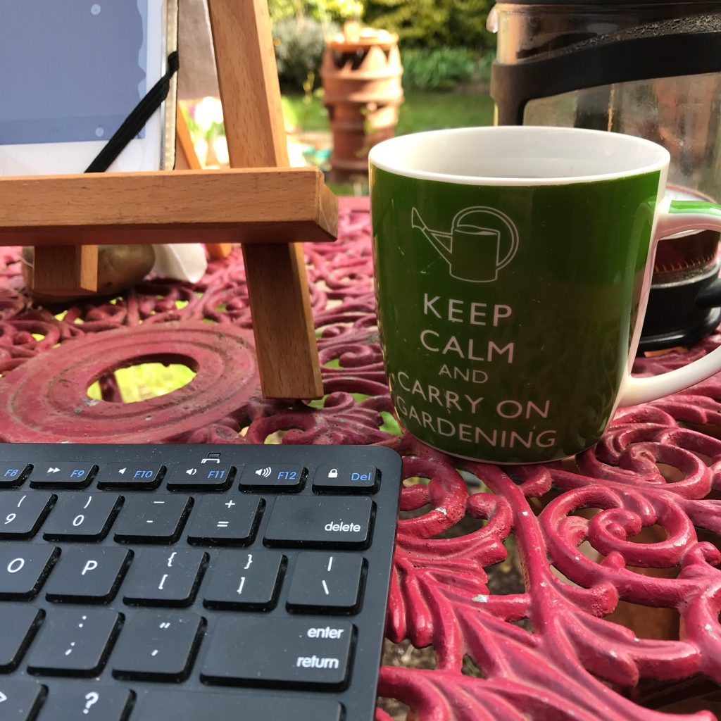 A coffee cup on a red bistro table in the garden, with keyboard and tablet ready for a gardening ways blog article